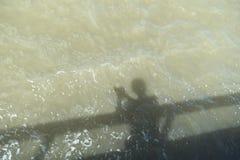 在水投下的人的阴影 免版税库存照片
