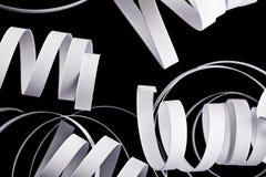 在黑抽象背景隔绝的卷毛丝带 免版税库存图片