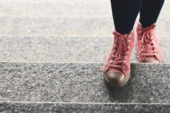 在黑攀登台阶的绑腿和桃红色运动鞋的妇女腿室外 免版税库存照片