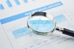在财政图和图表事务的放大镜 免版税图库摄影