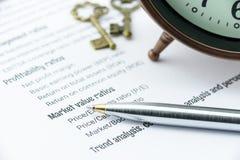 在财政比率分析清单上的蓝色圆珠笔与一个古色古香的时钟和两把葡萄酒黄铜钥匙 免版税库存照片
