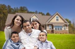 在他们新的家前面的年轻西班牙家庭 库存照片