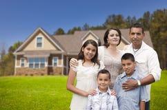 在他们新的家前面的年轻西班牙家庭 免版税库存照片