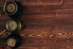 在破旧的土耳其罐cezve的热的咖啡与与拷贝空间的鲜美crema在棕色老木板背景,顶视图 库存图片