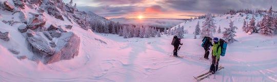 在黎明,人们去滑雪在冬天山全景 免版税库存图片