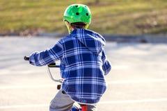 在黄昏太阳,从后面的看法的逗人喜爱的年轻男孩骑马自行车 库存照片