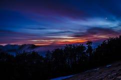 在黄昏期间的五颜六色的天空在mountiains 免版税库存图片