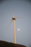 在黄昏期间的风轮机与后边月亮 免版税库存照片