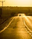 在黄昏的一条路与一辆aproaching的汽车 免版税库存照片