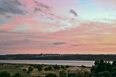 在黄昏的桃红色天空在瓜迪亚纳河,阿亚蒙特,西班牙 免版税库存照片