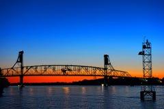 在黄昏的河流桥渡自动运输桥梁 图库摄影