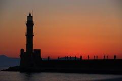 在黄昏的灯塔和人剪影 库存图片
