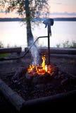 在黄昏的篝火在湖 库存图片