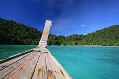 在水晶海的长尾巴木小船航行 图库摄影