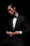 在黑暗与bowtie摆在供以座位的黑衣服的商人 免版税库存照片