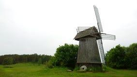 在阴暗条件的风车在一个绿色领域 库存图片