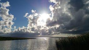 在黑暗的云彩上的明亮的太阳在湖 图库摄影