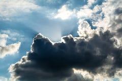 在黑暗的云彩后的太阳与蓝天 免版税库存图片