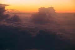 在黑暗的云彩的虚幻的日出通过窗口飞机 软绵绵地集中 免版税库存图片