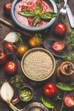 在黑暗的厨房用桌上的奎奴亚藜种子与烹调成份和西红柿酱,顶视图的菜 库存图片