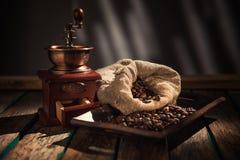 在黑暗的土气背景的咖啡碾 木表 图库摄影