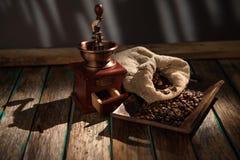 在黑暗的土气背景的咖啡碾 木表 免版税图库摄影