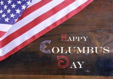 在黑暗的土气被回收的木头的愉快的哥伦布日问候文本 库存图片