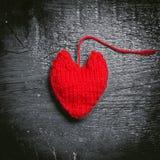 在黑暗的委员会的五颜六色的被编织的心脏 免版税库存照片