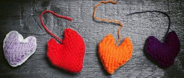 在黑暗的委员会的五颜六色的被编织的心脏 免版税图库摄影
