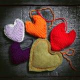 在黑暗的委员会的五颜六色的被编织的心脏 免版税库存图片