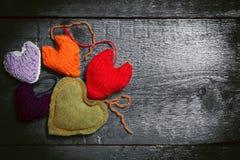 在黑暗的委员会的五颜六色的被编织的心脏 库存图片