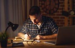 在黑暗的晚上供以人员在家研究计算机 免版税库存图片