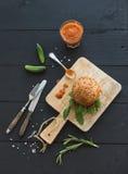 在黑暗的服务板的新鲜的自创汉堡用辣蕃茄sa 免版税库存图片