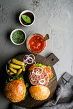 在黑暗的服务的新鲜的自创汉堡上用辣西红柿酱、绿色盐、胡椒、腌汁和葱 免版税库存图片