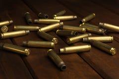 在黑暗的木板的空的步枪壳 库存照片