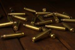 在黑暗的木板的空的步枪壳 库存图片