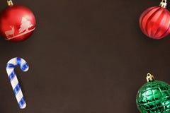 在黑暗的木桌上的圣诞节棍子,红色,波浪和绿色有肋骨球 免版税库存图片