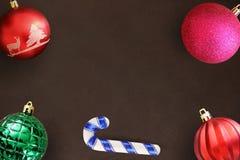 在黑暗的木桌上的圣诞节棍子,红色,波浪,桃红色和绿色有肋骨球 库存图片