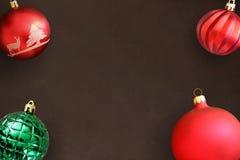 在黑暗的木桌上的圣诞节红色,波浪和绿色有肋骨球 免版税库存图片