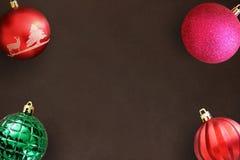 在黑暗的木桌上的圣诞节红色,波浪,桃红色和绿色有肋骨球 库存图片