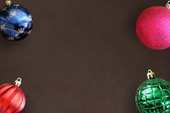 在黑暗的木桌上的圣诞节蓝色,桃红色,红色波浪和绿色有肋骨球 库存照片