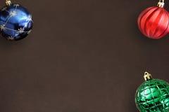 在黑暗的木桌上的圣诞节蓝色,红色,波浪和绿色有肋骨球 库存照片