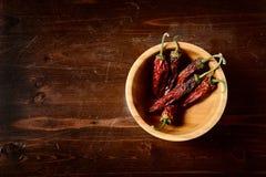 在黑暗的木桌上的干辣椒 免版税图库摄影