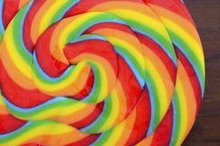 在黑暗的木桌上的明亮的彩虹棒棒糖糖果 库存图片