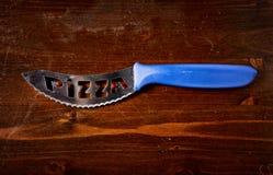 在黑暗的木桌上的薄饼刀子 免版税库存图片