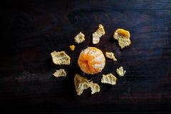 在黑暗的木桌上的被剥皮的蜜桔 免版税库存照片