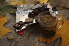 在黑暗的木桌热的绿茶,巧克力 秋天或冬天晚上 图库摄影