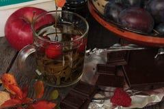 在黑暗的木桌热的绿茶,巧克力 秋天或冬天晚上 免版税图库摄影