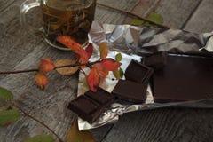 在黑暗的木桌热的绿茶,巧克力 舒适秋天或冬天晚上 库存图片