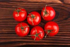在黑暗的木背景的一些个明亮的蕃茄 鲜美成熟夏天菜,特写镜头 菜夏天收获,顶视图 免版税库存照片